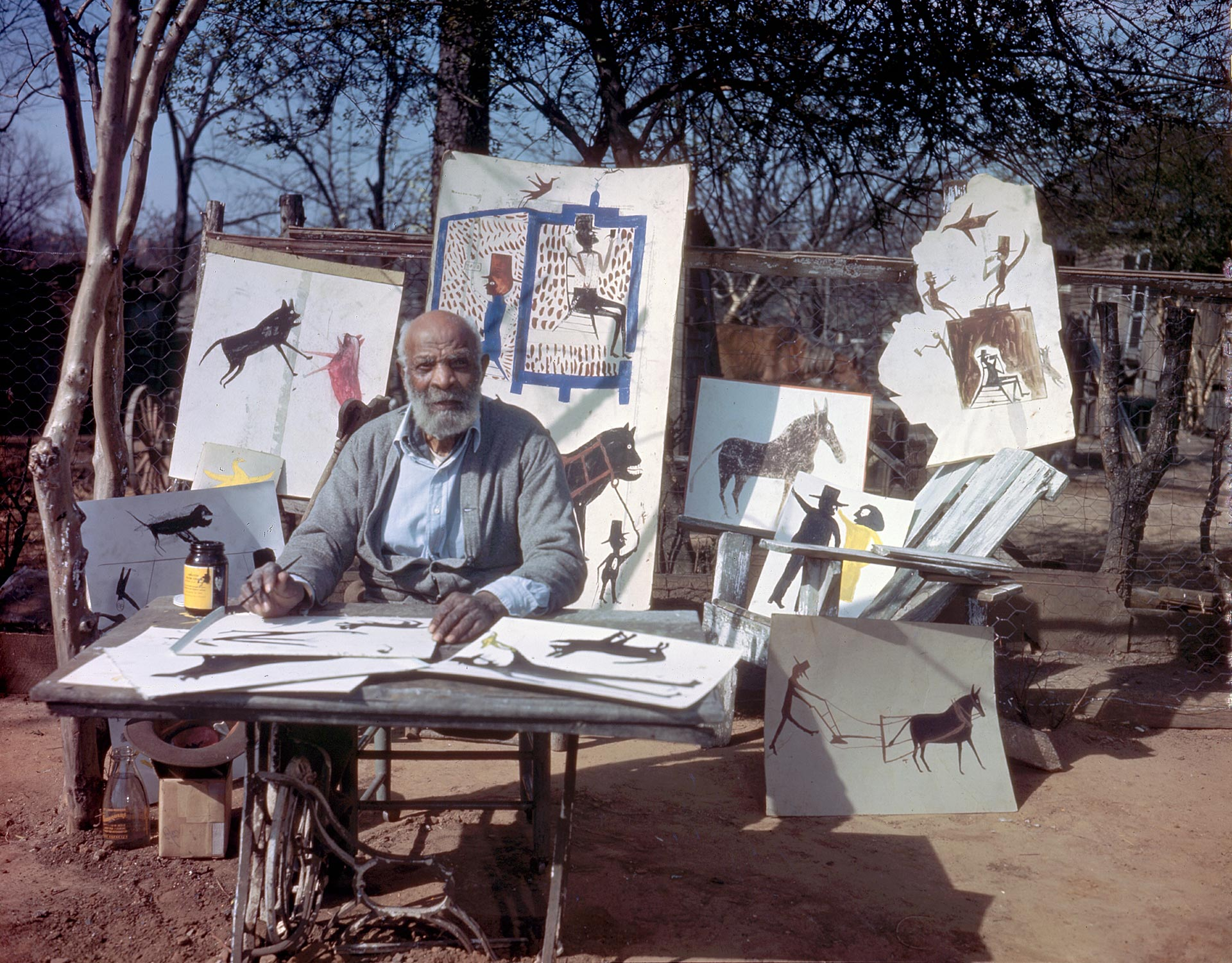 An archival photo of Bill Traylor working under a shade tree in a Montgomery neighborhood