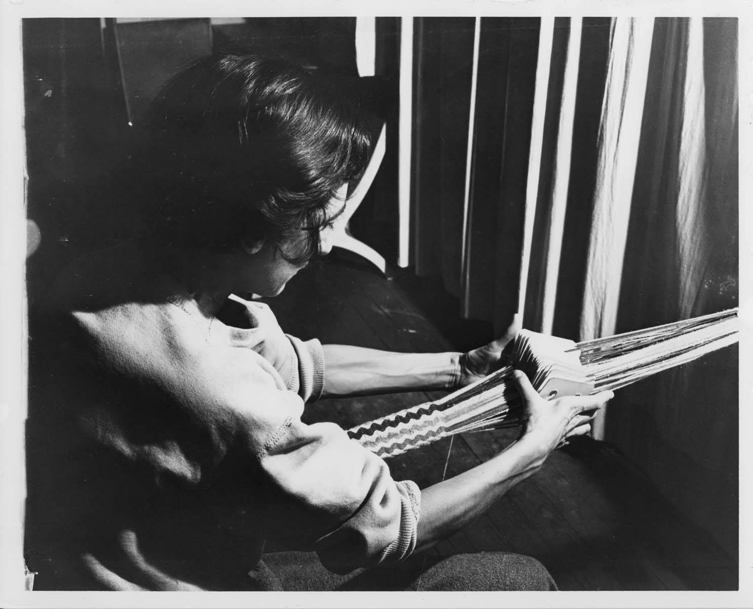 A photo of Anni Albers card weaving at Black Mountain College.