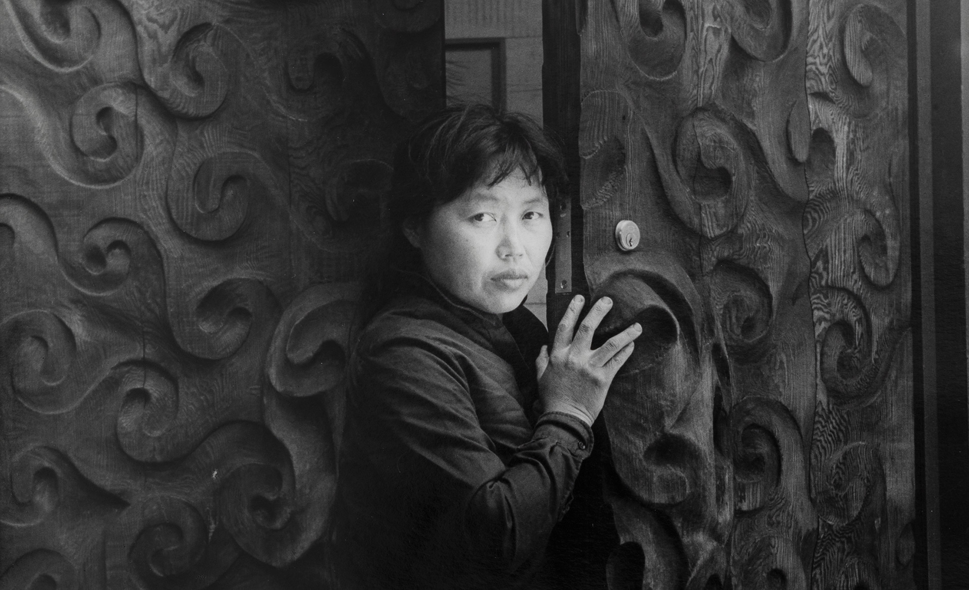 A photo by Imogen Cunningham of Ruth Asawa standing at her door, dated 1963.